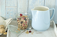 Glass of granola with dried blueberries and raspberries and a milk jug - ASF005853