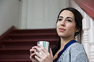 Daydreaming woman in staircase holding cup of coffee - FKF001688