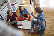 Three creative business people sitting on the floor discussing - FKF001697