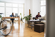Two creative business people working in informal office - FKF001715