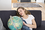 Portrait of daydreaming young woman sitting on couch looking at a globe - FMK002510