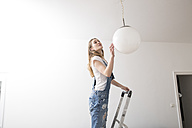 Young woman standing on a ladder checking ceiling light - FMKF002513