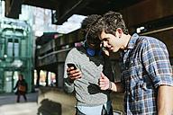 UK, London, two best friends watching something on smartphone - BOYF000122