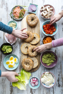 Breakfast, bagels, vegetables, salmon and ham, hands taking ingredients - SARF002624