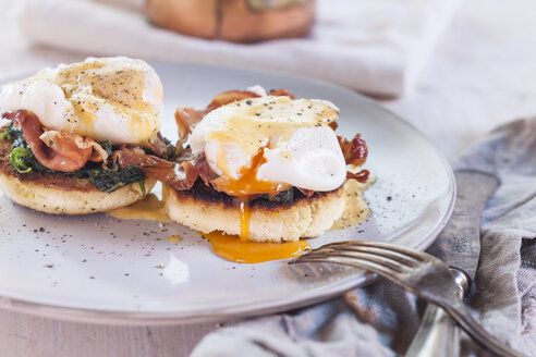 Egg Benedict with english muffins, poached eggs, ham, braised spinach, and Hollandaise - SBDF002713