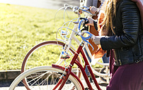Two young women strolling with bicycles - MGOF001477