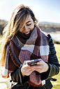 Smiling young woman using smartphone outdoors - MGOF001486