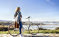 Spain, Gijon, smiling young woman on bicycle at the coast - MGOF001492