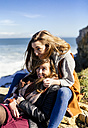 Spain, Gijon, two young women having fun near the sea - MGOF001495
