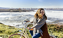 Spain, Gijon, happy young woman riding bicycle at the coast - MGOF001504
