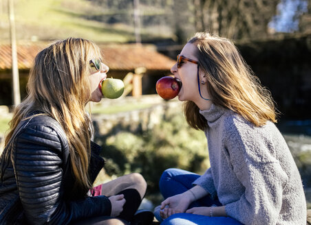 Two playful young women eating apples outside - MGOF001510