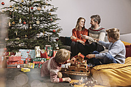 Family of four unwrapping Christmas gifts and playing with Noah's Ark - MFF002751