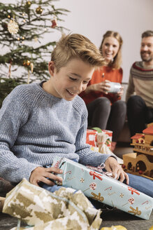Little boy unwrapping a Christmas gift, parents sitting on couch in background - MFF002757