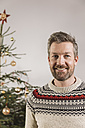Portrait of man in front of Christmas tree - MFF002769