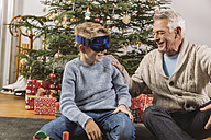 Happy grandfather looking at grandson's new ski glasses in front of Christmas tree - MFF002772