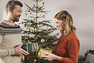 Couple exchanging Christmas gifts in front of tree - MFF002778