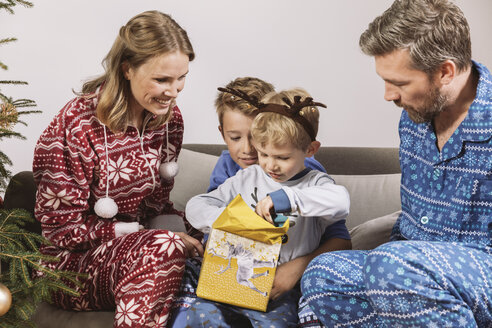 Parents watching son unwrapping a Christmas gift - MFF002784
