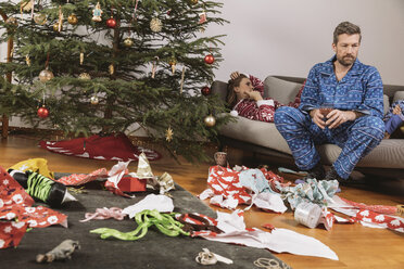 Tired couple in Christmas pyjamas looking at mess of wrapping paper - MFF002787