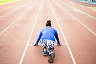 Female athlete training for race in stadium - KIJF000224