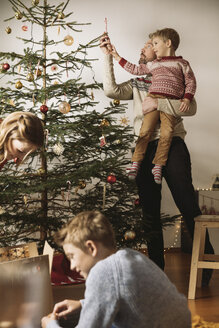 Family decorating Christmas tree - MFF002798