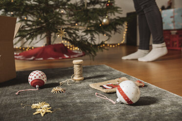 Christmas decoration lying on carpet, woman decorating tree in background - MFF002804