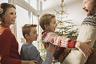 Happy family looking at Christmas tree - MFF002813