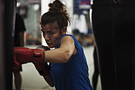 Female boxer exercising at punch bag - ZEDF000059