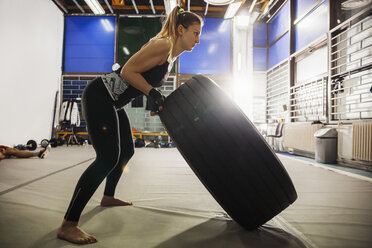 Woman exercising with tire in gym - ZEDF000068