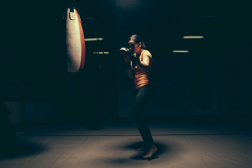 Female boxer exercising at punch bag - ZEDF000077