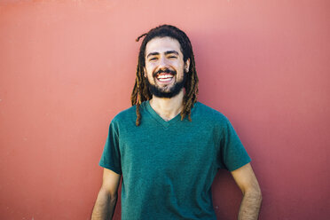 Portrait of laughing young man with dreadlocks and beard in front of a red wall - KIJF000232