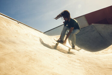 Young man with dreadlocks skateboarding in a skatepark - KIJF000235