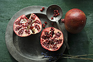 Two halves of pomegranate on tin plate - ASF005862