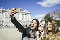 Spain, Madrid, three happy women taking a selfie with smartphone in front of royal palace - ABZF000265