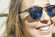 Friends of young woman reflecting at her sunglasses - ABZF000271