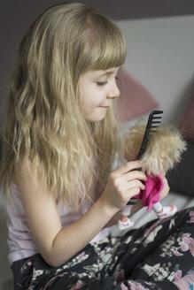 Little girl hairdressing her doll - JPF000118