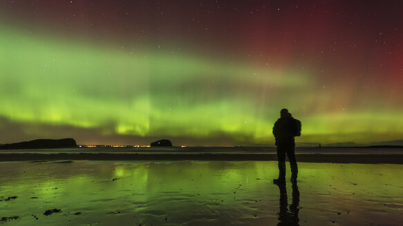 Scotland, East Lothian, silhouette of man standing on Seacliff Beach watching Northern lights - SMAF000444