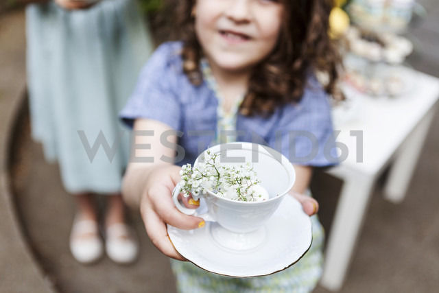 Girl playing tea time with an empty cup and blossoms - VABF000292