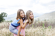 Spain, Girona, portrait of two happy sisters playing on a meadow - VABF000304