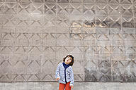 Little boy pulling funny faces in front of concrete wall - VABF000325