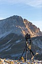 Italy, Abruzzo, Gran Sasso e Monti della Laga National Park, Camera on tripod in front of peak Corno Grande - LOMF000237