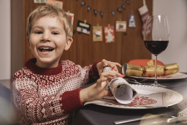 Happy boy at Christmas dinner table with Christmas crackers - MFF002829