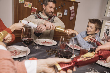 Pulling ends of Christmas crackers at family table - MFF002835