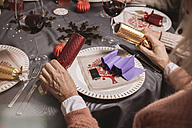 Senior woman holding two ends of Christmas crackers - MFF002838