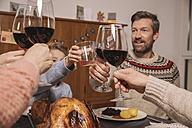 Family clinking glasses during Christmas dinner - MFF002847