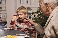 Grandfather comforting sad boy during Christmas dinner - MFF002850