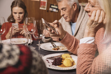 Family members playing with their smartphones after Christmas dinner - MFF002859