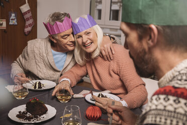 Happy senior couple with paper crowns having Christmas pudding - MFF002868