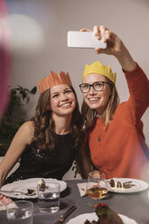 Two women with paper crowns taking a selfie while having Christmas pudding - MFF002871