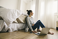 Relaxed woman sitting in bedroom using laptop - EBSF001240