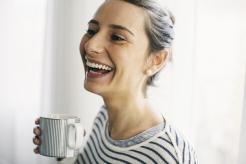 Laughing woman holding cup of coffee - EBSF001243